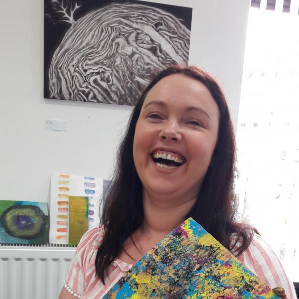 Sarah at The Brain Charity Art Workshop holding their painting