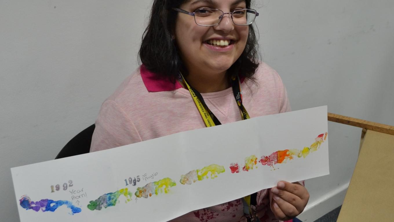 Amber holding up her NHS timeline at The Brain Charity Art Workshop