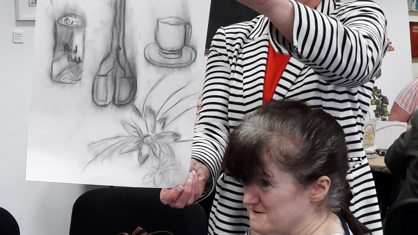 A participant at The Brain Charity Art Workshop with their still life drawing