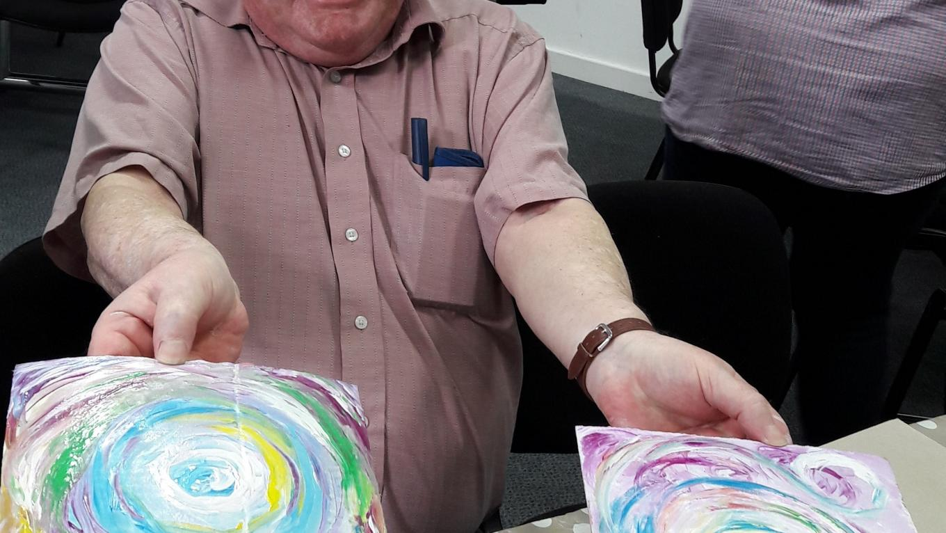 David at The Brain Charity Art Workshop holding their paintings