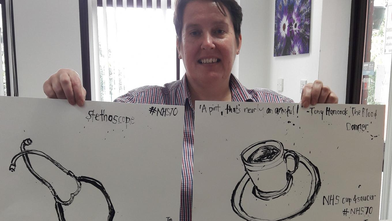 Linda at The Brain Charity Art Workshop holding their still life drawings