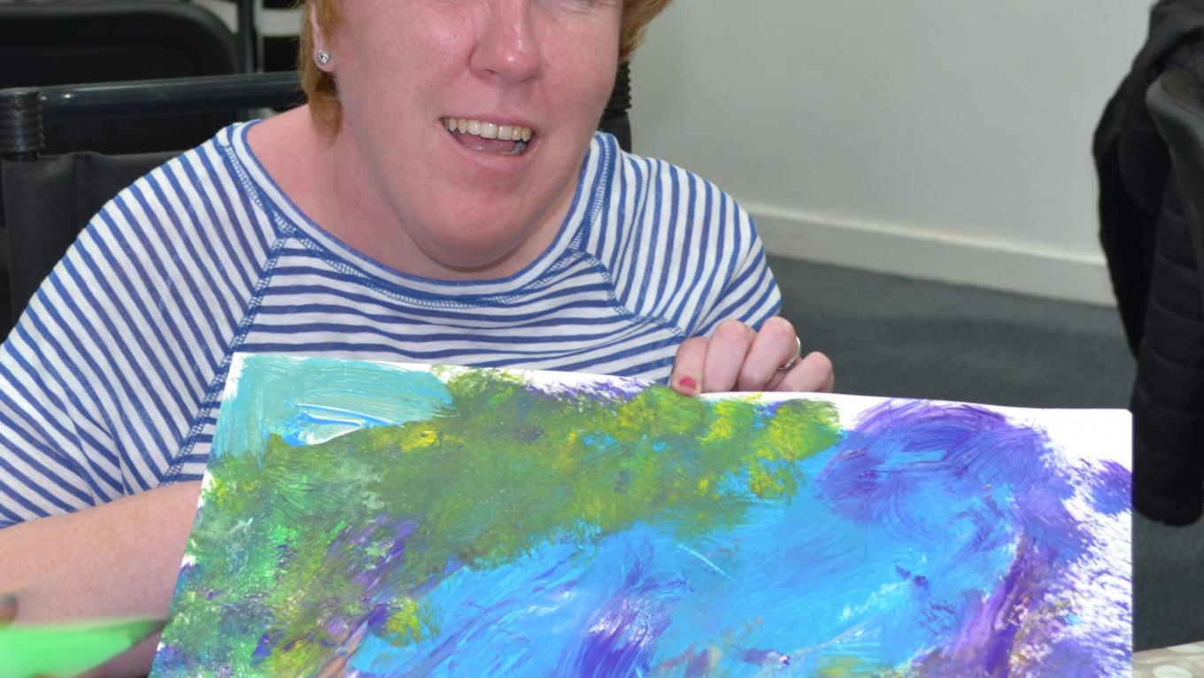 Christine at The Brain Charity Art Workshop holding their painting