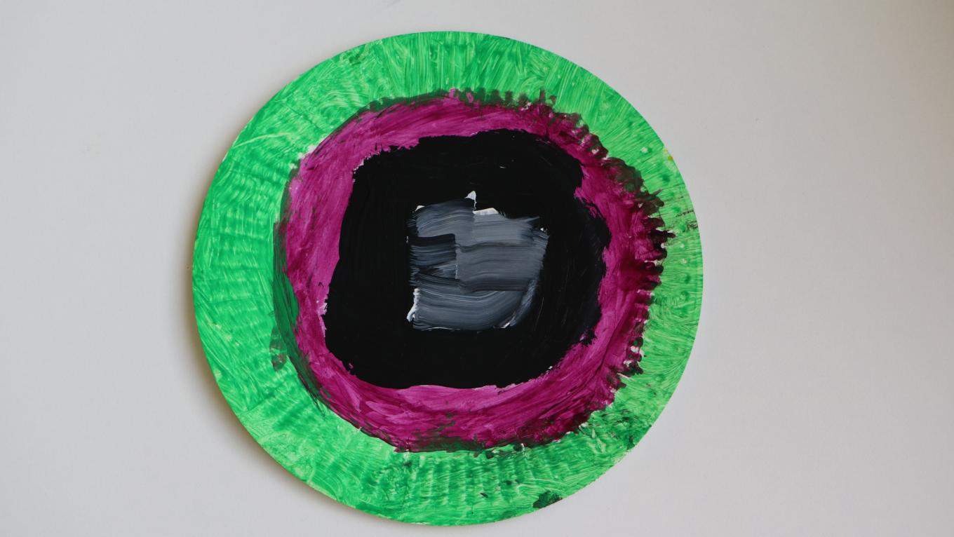 A painted paper plate, with black, red and green