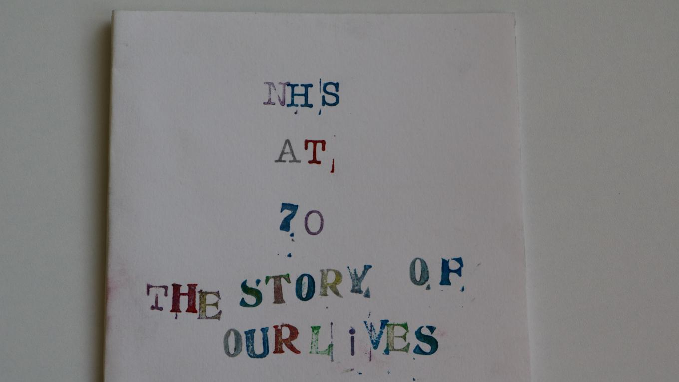 'NHS at 70, the Story of our Lives' stamped onto card